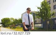 Купить «businessman with headphones riding scooter in city», видеоролик № 32027729, снято 5 августа 2019 г. (c) Syda Productions / Фотобанк Лори