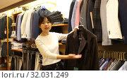 Купить «Competent young saleswoman offering various interesting cloth in textile shop», видеоролик № 32031249, снято 6 июня 2019 г. (c) Яков Филимонов / Фотобанк Лори