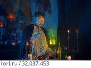 Купить «portrait of wizard with burning candles and magic potions», фото № 32037453, снято 14 августа 2019 г. (c) Майя Крученкова / Фотобанк Лори