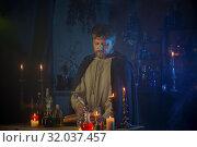 Купить «portrait of wizard with burning candles and magic potions», фото № 32037457, снято 14 августа 2019 г. (c) Майя Крученкова / Фотобанк Лори
