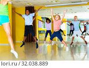 Купить «Group of tweens jumping with female coach during exercising in c», фото № 32038889, снято 31 июля 2019 г. (c) Яков Филимонов / Фотобанк Лори