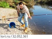 Купить «Adult man standing near river and pulling fish expressing emotions of dedication», фото № 32052361, снято 15 марта 2019 г. (c) Яков Филимонов / Фотобанк Лори