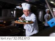 Купить «Young chef holding shovel with cooked pizza», фото № 32052613, снято 2 ноября 2018 г. (c) Яков Филимонов / Фотобанк Лори