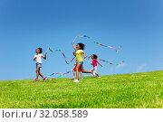 Купить «Group of girls run fast waving with color ribbons», фото № 32058589, снято 15 июня 2019 г. (c) Сергей Новиков / Фотобанк Лори