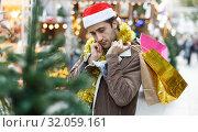 Man choosing decorations and Christmas tree at Christmas market. Стоковое фото, фотограф Яков Филимонов / Фотобанк Лори