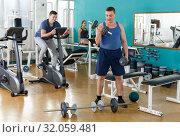 Купить «Portrait of man lifting dumbbells at gym», фото № 32059481, снято 5 ноября 2018 г. (c) Яков Филимонов / Фотобанк Лори
