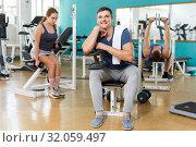 Купить «Man sitting on training apparatus», фото № 32059497, снято 5 ноября 2018 г. (c) Яков Филимонов / Фотобанк Лори
