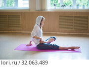 Young acrobatic woman with blonde hair sitting on the yoga mat and begin to sit in the lotus pose. Стоковое фото, фотограф Константин Шишкин / Фотобанк Лори