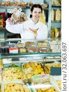 Купить «Seller in white uniform with dark cookies», фото № 32063697, снято 22 марта 2017 г. (c) Яков Филимонов / Фотобанк Лори