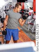 Купить «Portrait of muscular guy lifting dumbbells», фото № 32063729, снято 15 октября 2018 г. (c) Яков Филимонов / Фотобанк Лори