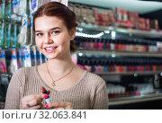 Купить «Smiling woman customer browsing rows of lipstick», фото № 32063841, снято 21 февраля 2017 г. (c) Яков Филимонов / Фотобанк Лори