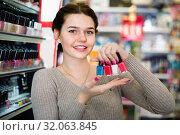 Купить «Smiling woman customer deciding on nail polish», фото № 32063845, снято 21 февраля 2017 г. (c) Яков Филимонов / Фотобанк Лори