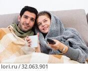 Купить «Happy couple nestling on couch watching TV», фото № 32063901, снято 12 ноября 2019 г. (c) Яков Филимонов / Фотобанк Лори