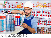 Купить «Focused workman choosing materials for renovation works in paint store», фото № 32063917, снято 13 сентября 2017 г. (c) Яков Филимонов / Фотобанк Лори