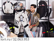 Купить «man is choosing new pants for motorbike in the moto store.», фото № 32063953, снято 1 сентября 2017 г. (c) Яков Филимонов / Фотобанк Лори