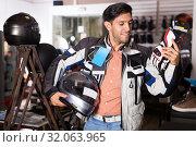 Купить «customer in jacket with helmet is choosing gloves», фото № 32063965, снято 1 сентября 2017 г. (c) Яков Филимонов / Фотобанк Лори