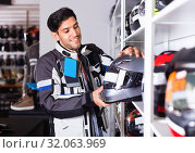 Купить «Male customer is choosing modern helmet near shelves», фото № 32063969, снято 1 сентября 2017 г. (c) Яков Филимонов / Фотобанк Лори