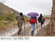 Villagers returning from the village of Tighza crossing the river under the snow, Ounila River valley, Ouarzazate Province, region of Draa-Tafilalet, Morocco, North West Africa. (2019 год). Редакционное фото, фотограф Christian Goupi / age Fotostock / Фотобанк Лори