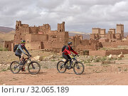 Riders on mountain bike with electric assistance in front of the Ksar of Tamedakhte, Ounila River valley, Ouarzazate Province, region of Draa-Tafilalet, Morocco, North West Africa. (2019 год). Редакционное фото, фотограф Christian Goupi / age Fotostock / Фотобанк Лори