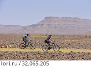 Mountain bikers with electric assistance on a trail through the reg, from Agdz to Zagora, Draa River valley, Province of Zagora, Region Draa-Tafilalet, Morocco, North West Africa. (2019 год). Редакционное фото, фотограф Christian Goupi / age Fotostock / Фотобанк Лори