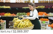 Купить «Portrait of young smiling saleswoman with yellow bananas in store», видеоролик № 32069397, снято 12 февраля 2019 г. (c) Яков Филимонов / Фотобанк Лори