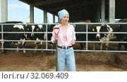 Купить «Portrait of successful young female breeder standing in cowshed», видеоролик № 32069409, снято 9 июня 2019 г. (c) Яков Филимонов / Фотобанк Лори