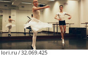 Купить «Choreographer woman and young man do exercises at ballet bar in hall with mirror», видеоролик № 32069425, снято 26 мая 2019 г. (c) Яков Филимонов / Фотобанк Лори
