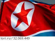 Купить «Государственный флаг Корейской Народно-Демократической Республики развивается на ветру», фото № 32069449, снято 23 августа 2019 г. (c) Николай Винокуров / Фотобанк Лори