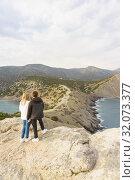 Парень и девушка стоят на мысе Капчик и смотрят на горы Коба-Кая (Пещерная, или Орел) и Караул-Оба и бухты - Синюю (Разбойничью) и Голубую (Делилиманскую, Царскую). Пасмурный день весны (2019 год). Стоковое фото, фотограф Наталья Гармашева / Фотобанк Лори
