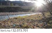Купить «Dolly slider shot of the splashing water in a mountain river near forest. Wet rocks and sun rays. Horizontal steady movement. Raw flat colors.», видеоролик № 32073701, снято 5 октября 2018 г. (c) Александр Маркин / Фотобанк Лори