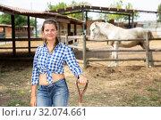Купить «Smiling woman near enclosure with horses», фото № 32074661, снято 17 ноября 2019 г. (c) Яков Филимонов / Фотобанк Лори