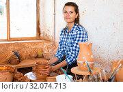 Купить «Female artisan in ceramics workshop with pottery wheel and various clay vessels», фото № 32074713, снято 19 ноября 2019 г. (c) Яков Филимонов / Фотобанк Лори