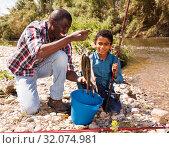 Купить «Man and boy with fish catch», фото № 32074981, снято 26 мая 2019 г. (c) Яков Филимонов / Фотобанк Лори