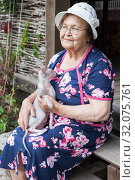 Купить «Elderly Caucasian lady with hat and eyeglesses sitting on stair with sphynx cat on knees, county woman», фото № 32075761, снято 20 июля 2019 г. (c) Кекяляйнен Андрей / Фотобанк Лори