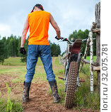 Купить «Rear view of cross-country motorcycle racer with his motocross bike, man standing countryside near fence», фото № 32075781, снято 20 июля 2019 г. (c) Кекяляйнен Андрей / Фотобанк Лори