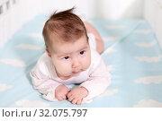 Двухмесячный ребенок в кроватке на животе. Стоковое фото, фотограф Кекяляйнен Андрей / Фотобанк Лори