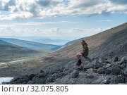 Contemplative man hiker sitting on stone of mountain peak at early morning, seen pleasant outlook over mountains. Стоковое фото, фотограф Кекяляйнен Андрей / Фотобанк Лори