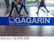 """Вход в аэропорт Гагарин, Саратов. Пассажиры идут мимо ленты с надписью """"Gagarin Saratov International Airport"""" Редакционное фото, фотограф 1Andrey Милкин / Фотобанк Лори"""