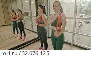Купить «Two healthy women standing in the studio and training their hand with a stretching strap», видеоролик № 32076125, снято 29 мая 2020 г. (c) Константин Шишкин / Фотобанк Лори