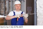 Купить «Builder working with drill», фото № 32076681, снято 28 мая 2018 г. (c) Яков Филимонов / Фотобанк Лори
