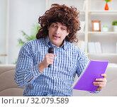 Купить «Funny man singing songs in karaoke at home», фото № 32079589, снято 29 марта 2017 г. (c) Elnur / Фотобанк Лори