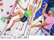 Купить «Couple of alpinist practicing in pair indoor rock-climbing», фото № 32081961, снято 29 февраля 2020 г. (c) Яков Филимонов / Фотобанк Лори