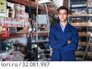 Portrait of man seller in uniform standing near shelving. Стоковое фото, фотограф Яков Филимонов / Фотобанк Лори