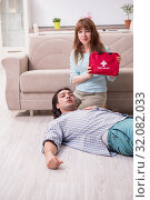 Купить «Young couple in first aid concept at home», фото № 32082033, снято 10 мая 2019 г. (c) Elnur / Фотобанк Лори