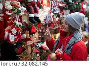 Купить «Girl shopping Christmas decorations», фото № 32082145, снято 1 декабря 2018 г. (c) Яков Филимонов / Фотобанк Лори