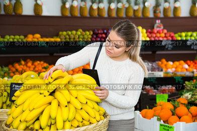 Girl choosing fruits in grocery