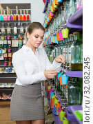 Купить «Young saleswoman pouring perfume from large bottle with tap in perfume shop», фото № 32082245, снято 24 апреля 2018 г. (c) Яков Филимонов / Фотобанк Лори