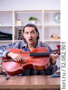 Купить «Young handsome repairman repairing cello», фото № 32082901, снято 4 апреля 2019 г. (c) Elnur / Фотобанк Лори