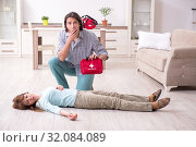 Купить «Young couple in first aid concept at home», фото № 32084089, снято 10 мая 2019 г. (c) Elnur / Фотобанк Лори