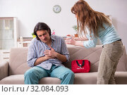 Купить «Young couple in first aid concept at home», фото № 32084093, снято 10 мая 2019 г. (c) Elnur / Фотобанк Лори